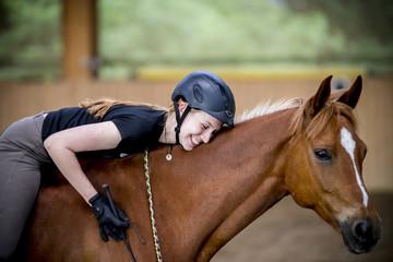 Junge Frau umarmt ihr Pferd und ist glücklich