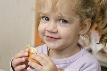 Девочка с удовольствием ест булочку