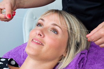 woman having threading hair removal procedure