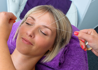 woman having threading hair removal procedure