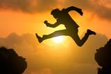 Silhouette businessman jump through the gap
