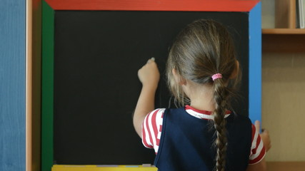 pupil draws a chalk on a school blackboard flower