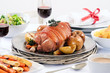 Pork roast dinner with vegetable, potato sides and wine