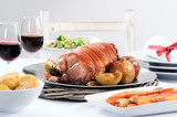 Pork roast dinner with vegetable, potato sides and wine for chri