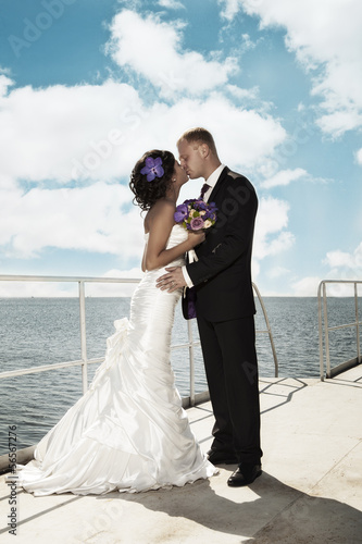 Newlyweds kissing on the pier