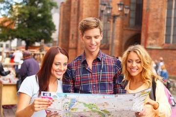 Three friends tourist with map outdoors