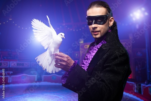 Young magician man in stage costume