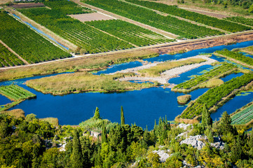 Fertile Neretva valley with crops and lakes