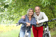 Cheerful senior couple with bicycle in country path - 56571471