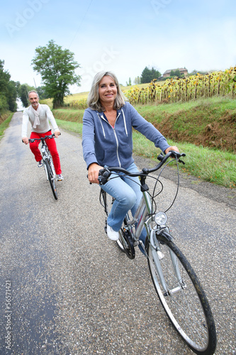 Senior couple riding bicycle in countryside