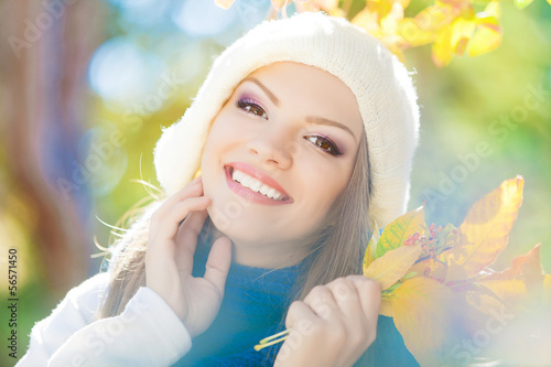 happy fall woman smiling and holding autumn leaves