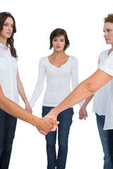 Pensive women standing and holding hands in a circle