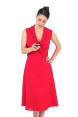 Elegant brunette in red dress sending text message