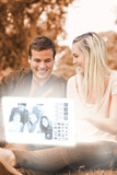 Happy young couple watching photos on digital interface
