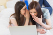 Girl telling a secret to her friend in front of laptop