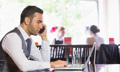Serious businessman man calling on phone using laptop