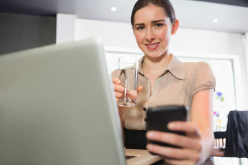 Smiling businesswoman holding glass of water and phone in a cafe