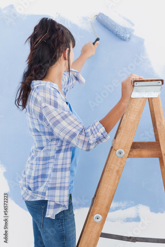 Woman using paint roller to paint wall blue