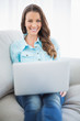 Cheerful brunette sitting on sofa using laptop