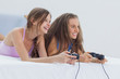 Excited girls playing video games on bed