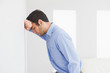 Sad man leaning his head against a wall