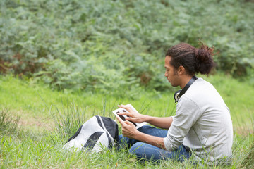 Man Using Digital Tablet Whilst Hiking In Countryside