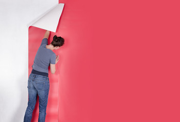 Woman hanging red wallpaper on white wall. Decorating or paperin