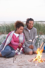 Couple Camping On Beach And Toasting Marshmallows