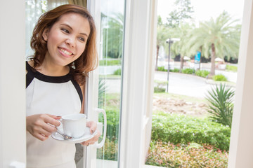 Woman holding her coffee cup at the porch