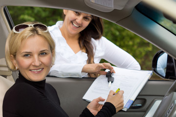 Happy woman signing for her new car