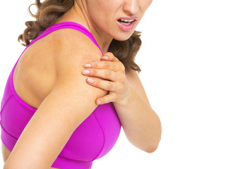 Closeup on fitness woman having pain in shoulder