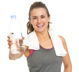 Smiling fitness young woman with towel giving bottle of water