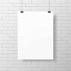 Blank white poster hanging on brick wall