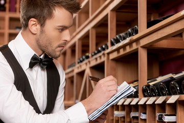 Confident sommelier. Side view of confident young sommelier writ
