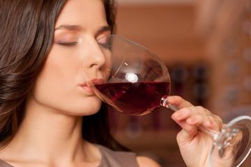 Woman drinking wine. Beautiful young woman drinking wine and kee