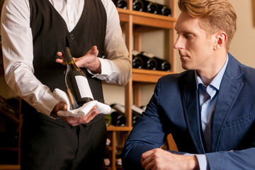 Sommelier and customer. Sommelier showing a wine bottle to custo