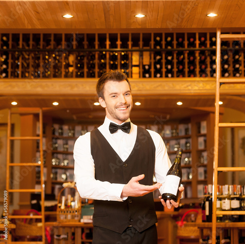 Confident sommelier. Cheerful young sommelier holding a wine bot