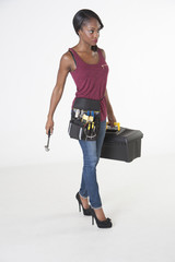 Female worker walking with toolbox