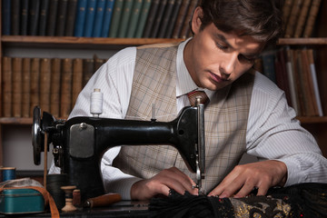 Tailor at work. Confident young man working at the tailor shop