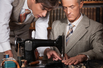 Tailors at work. Two confident tailors working at tailor shop
