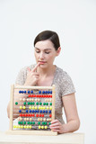 Puzzled Woman Using Abacus