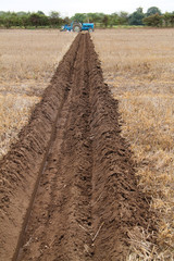 A Blue Tractor at the End of a Ploughed Field Furrow.