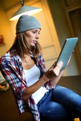 Hipster girl websurfing on tablet in kitchen