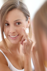 Young woman applying  anti-wrinkles cream