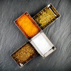Epices et condiments dans des ramequins sur ardoise grise