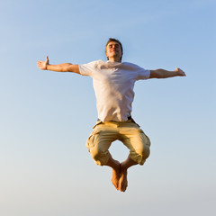 Happy young man jumping against blue sky at sunset