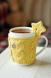 Hot tea in a mug, wrapped in a knitted cup-holder