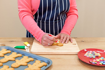 Woman decorating gingerbread men