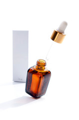 Pipette with drop of cosmetic oil above brown bottle with box