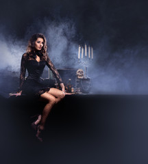 A young and sexy witch in a black dress on a smoky background